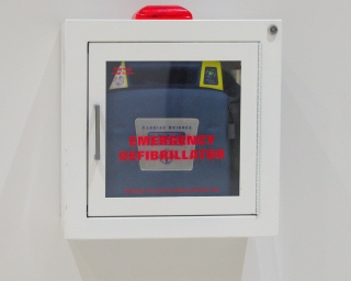 Picture of an Automated External Defibrillator mounted to a wall.