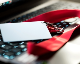 View an ID card and lanyard draped over a keyboard.