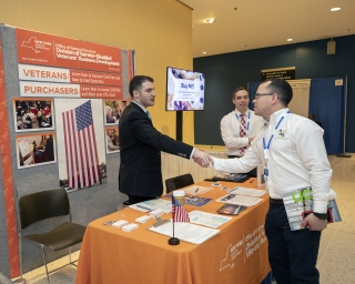 Service-Disabled Veterans program staff shaking hands with a customer at the 2018 GovBuy.