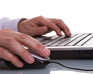 Close-up of a man's hands using a keyboard and mouse.