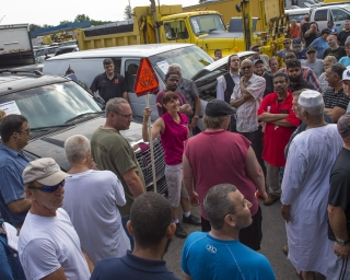 A crowd of people participating in a live vehicle auction.