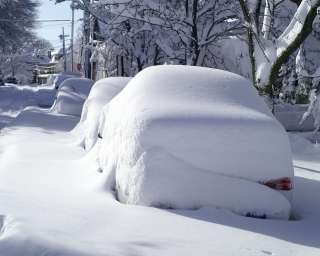 Snow covered cars parked on a street covered in a significant snowfall