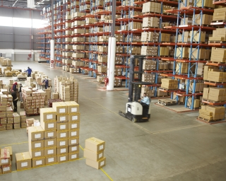Warehouse with boxes on shelves and a forklift working