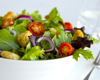 A bowl of salad with lettuce, tomatoes and onions.