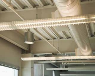 View of lighting fixtures hanging from a ceiling in an office setting.