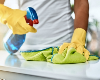 Person with gloves spraying a cleaner on a surface and wiping.
