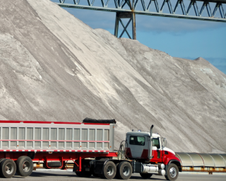A huge mound of road salt that dwarfs a semi truck.