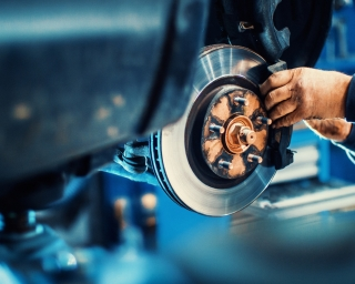 View of an automotive mechanic installing brake pads on a car.