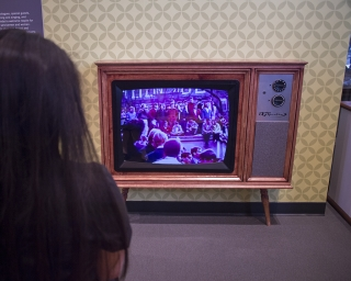 A woman looks at a video in a retro TV set at the 1969 Exhibit.
