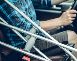 Close-up of man sitting in car behind the steering wheel with crutches in the passenger seat.