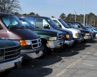Row of trucks and vans in a parking lot ready for auction.