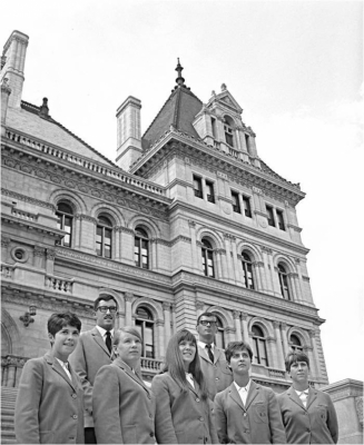 Tour guides from the 1960s standing on the steps of the New York State Capitol.