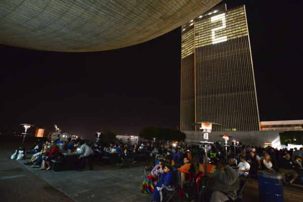 Visitors watch Jeter's last game at the Plaza while the Corning Tower is lit up for Jeter's number 2.