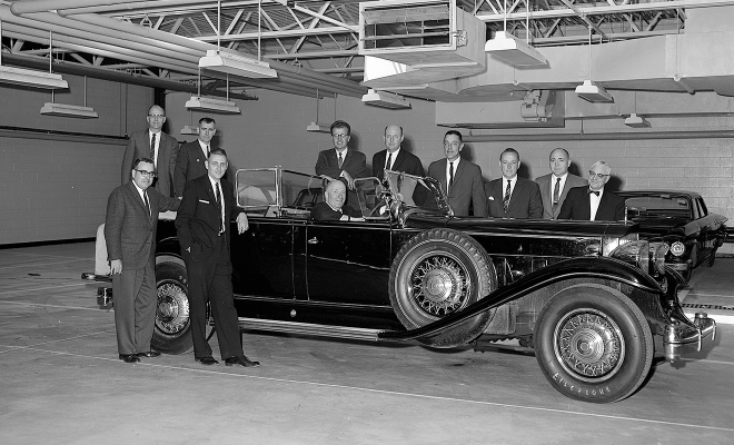 Group posing in and around Packard car.